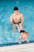 plavecký trenér v čepici drží nohy veselého batole chlapce v bazénu