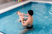 šťastný plavecký trenér v plavání čepice držení v náručí veselý batole chlapec