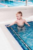 roztomilý batole chlapec v bazénu s modrou vodou