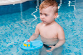Photo cute toddler boy playing with toy ship in swimming pool
