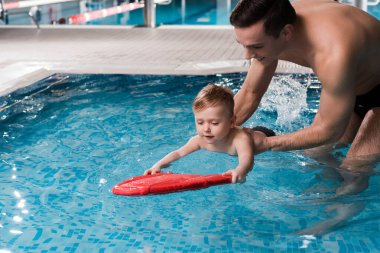 happy swim coach teaching toddler kid with flutter board in swimming pool