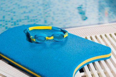 goggles on flutter board near swimming pool with blue water