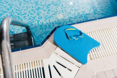top view of swim goggles on flutter board near swimming pool