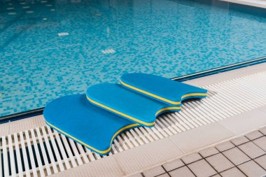 blue flutter boards near swimming pool in sports center