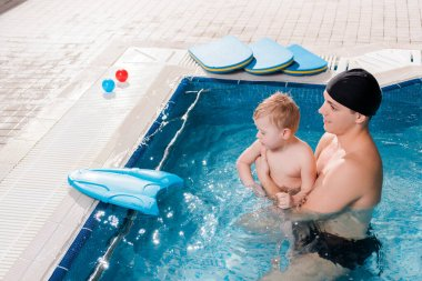 side view of cheerful swim coach swimming with toddler kid in swimming pool
