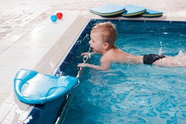 happy toddler boy swimming near flutter boards in swimming pool