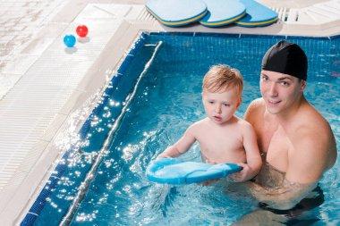 happy swim coach in swimming cap teaching toddler kid in swimming pool