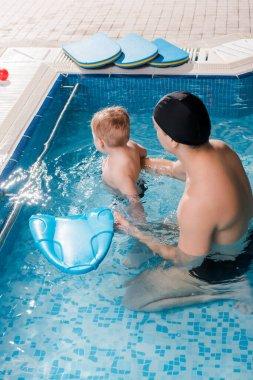 swim coach in swimming cap swimming with toddler kid in swimming pool