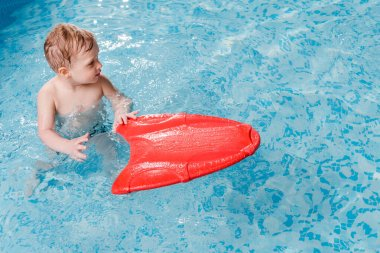 cute toddler boy swimming with flutter board in swimming pool