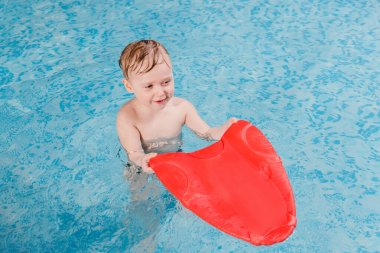 happy toddler boy swimming with flutter board in swimming pool