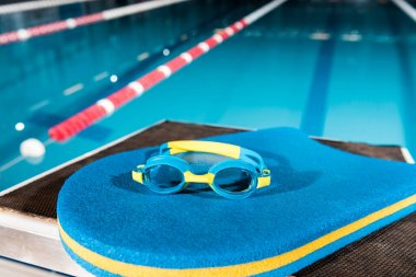 goggles on blue flutter board near swimming pool