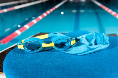 goggles and swimming cap on flutter board near swimming pool with blue water
