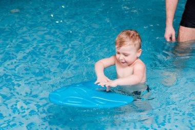 cute toddler boy swimming with flutter board near swim coach