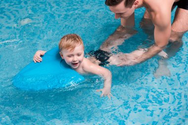 excited toddler boy swimming with flutter board near swim coach