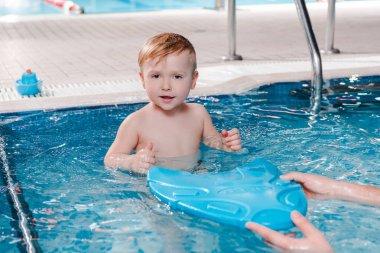 swim trainer holding flutter board near cute toddler boy in swimming pool