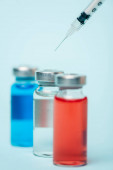 Selective focus of syringe near jars with colored hormonal drugs on blue surface