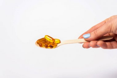Cropped view of woman holding wooden spoon with pills of omega 3 isolated on white