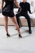 Fotografie Teilansicht einer Frau mit Peitsche vor einem Mann, der im Schlafzimmer auf dem Bett sitzt