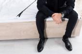 Oříznutý pohled na muže v blízkosti bičování bičem sedí na posteli