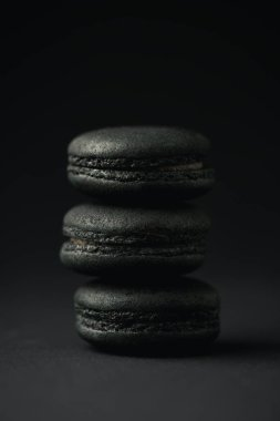 Sweet and dark macarons on black with copy space stock vector