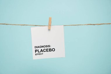 Card with diagnosis placebo effect lettering on rope with pin isolated on blue stock vector