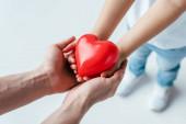 oříznutý pohled adoptovaného dítěte a rodiče držícího červené srdce na bílém