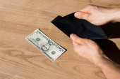 cropped view of man holding empty wallet near dollar banknote