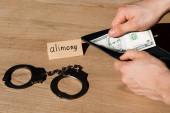 levágott kilátás férfi tartó pénztárca és dollár bankjegy mellett papír tartásdíj betűkkel és bilincsekkel