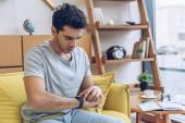 Muž se dívá na hodinky na pohovce v obývacím pokoji