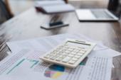 Kalkulačka s papíry na stole v kanceláři