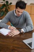 Válogatott fókusz az üzletember írás ceruzával notebook közelében laptop asztalnál