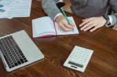 Oříznutý pohled obchodníka na psaní v notebooku u notebooku, kalkulačky a papíry u stolu v kanceláři