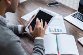 Oříznutý pohled na podnikatele pracující s digitálním tabletem u stolu v kanceláři