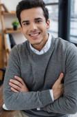 Podnikatel se zkříženýma rukama se dívá do kamery a usmívá