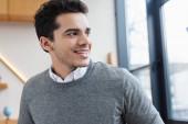 Portrét obchodníka, jak se dívá jinam a usmívá se v kanceláři