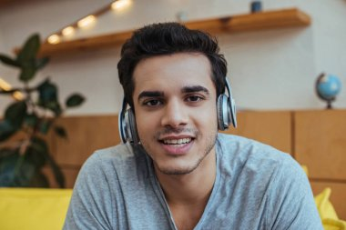 Man in headphones smiling and looking at camera
