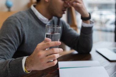 Cropped view of businessman with headache holding glass of water in office