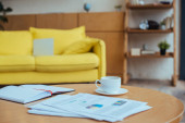 Couchtisch mit Papieren, Tasse Kaffee und Notizbuch im Wohnzimmer