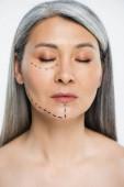 atraktivní nahá asijská žena se zavřenýma očima a plastickou chirurgickou korekcí na tváři izolované na šedé