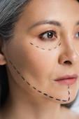 schöne asiatische Frau mit plastischen Chirurgie Korrekturzeichen auf dem Gesicht isoliert auf grau