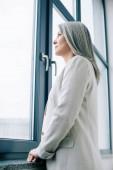 atraktivní asijské podnikatelka s šedými vlasy při pohledu z okna