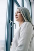 přemýšlivá asijská podnikatelka s šedými vlasy v šedém obleku dívá oknem