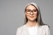 atraktivní usměvavá asijská podnikatelka v brýlích izolované na šedé