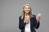 emotivní asijské podnikatelka s kávou jít poslouchat hudbu se sluchátky a smartphone izolované na šedé