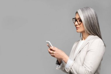 Beautiful asian businesswoman in eyeglasses with grey hair talking on smartphone isolated on grey stock vector
