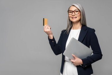 Happy asian businesswoman with grey hair shopping online with credit card and laptop isolated on grey stock vector