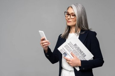 Confident asian businesswoman in eyeglasses using smartphone and holding business newspaper isolated on grey stock vector