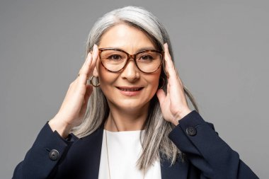 Smiling asian businesswoman with grey hair in eyeglasses isolated on grey stock vector