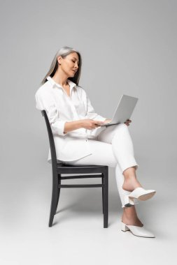 Adult attractive asian woman with grey hair sitting on chair and using laptop on grey stock vector