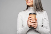 cropped view of woman in turtleneck with grey hair holding coffee to go isolated on grey